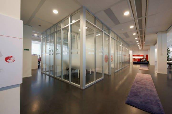 Door het plaatsen van systeemwanden worden losse vergaderkamers gecreëerd op kantoor