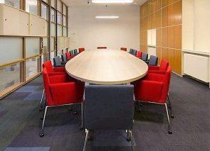 Ovale vergadertafel met comfortabele vergaderstoelen op wielen