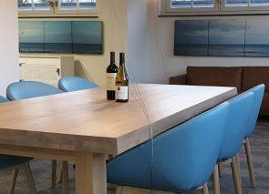 Robuste houten vergadertafel met blauwe lederen kuipstoelen