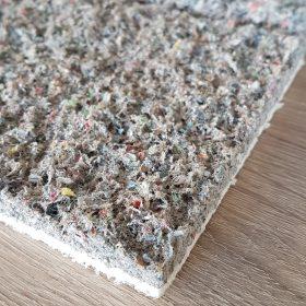 Detail van gerecycled krantenpapier dat gebruikt wordt om plafonds akoestisch te dempen