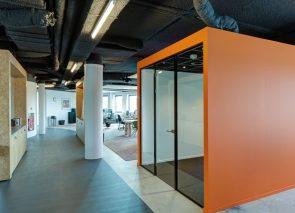 Donker spuitwerk op plafond in industrieel kantoorpand voor verbetering van akoestiek
