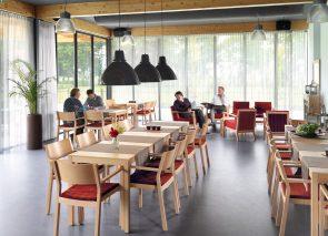 Houten zorgstoel en met rodse bekleding met bijpassende tafels