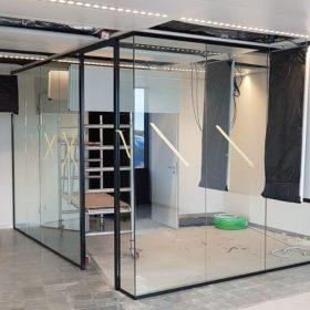 Werk in uitvoering plaasing van glaswanden met zwarte omlijsting