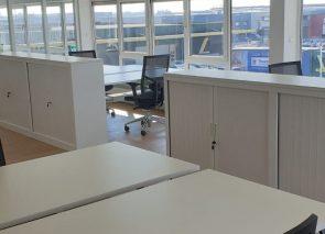 Witte schuifdeurkasten en sta-zit bureau's geplaatst