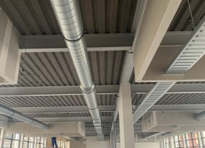 Akoestisch spuitplafond aangebracht voor verbetering van de akoestiek in dit industriële pand