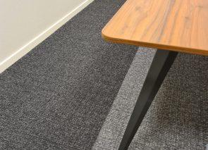 Detail van de vergadertafel in combinatie met het tapijt