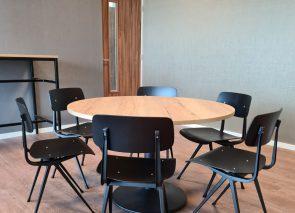 Ronde tafel met zwarte schoolstoeltjes in de kantine van DSV