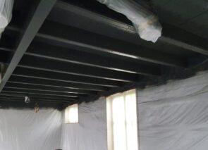 De houten balken plafonds worden gespoten in een donker grijze tint en de muren en pilaren wit