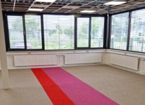 De huisstijlkleuren komen terug in het tapijt