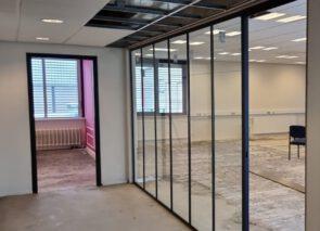 Glaswanden met zwarte kozijnen zijn geplaatst - het kantoor begint al vorm te krijgen