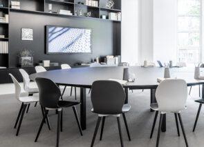 ronde vergadertafel met eenvoudige vergaderstoelen strak uitgevoerd in zwart en wit